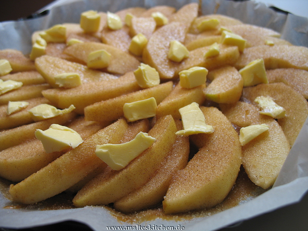Auf die Apfelspalten kommt der Zimtzucker und die Butterflocken