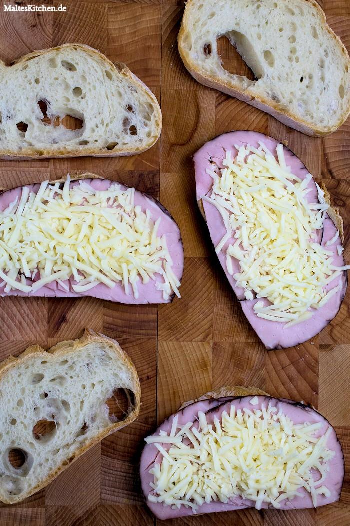 Das Baguette wird mit Mayo, Schinken und Käse belegt.
