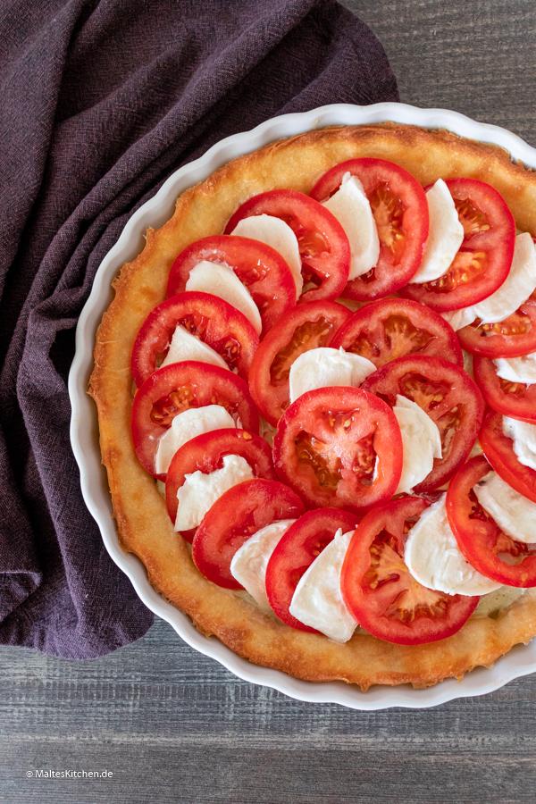 Der Boden wird mit Tomaten und Mozzarella belegt