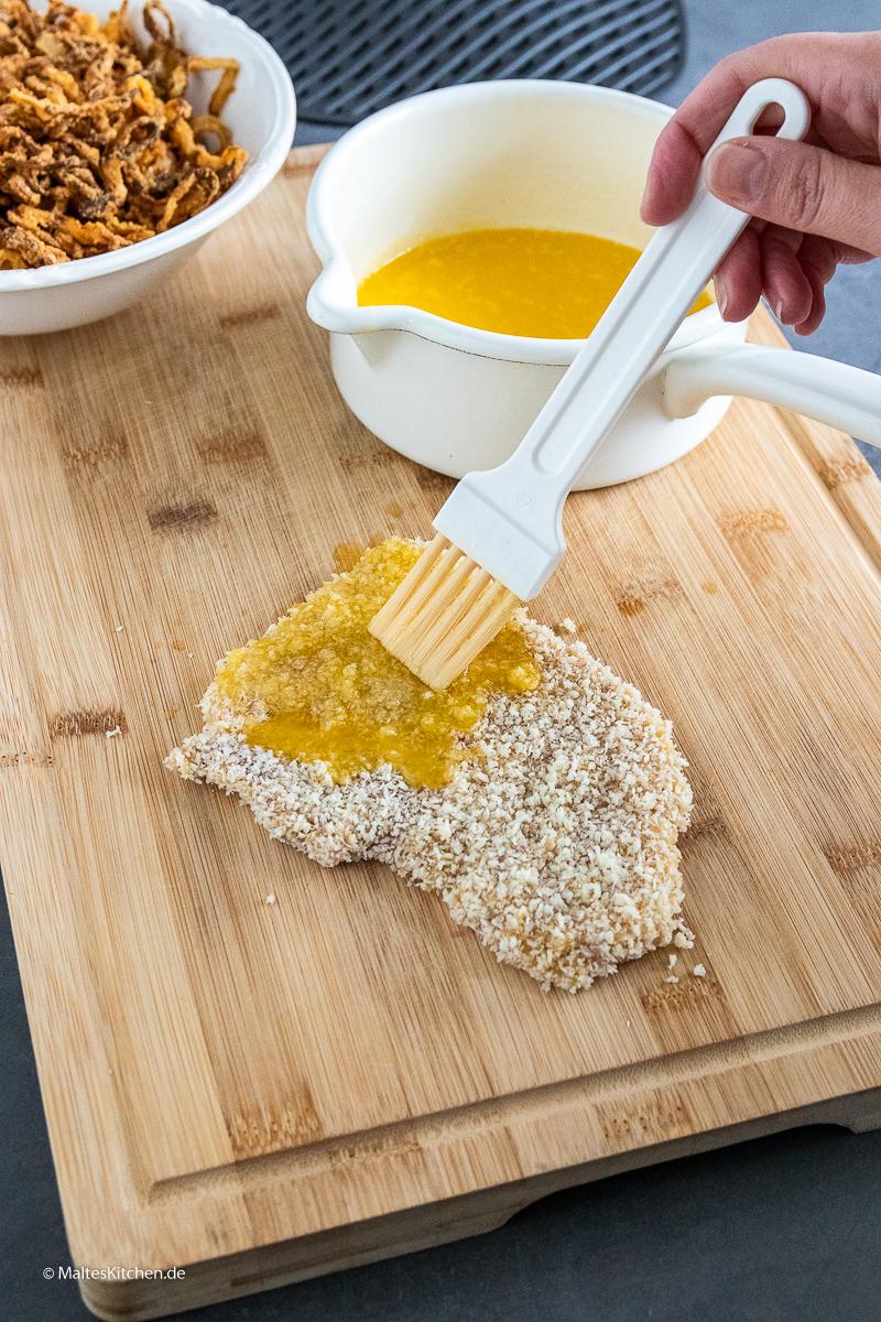 Das Schnitzel wird mit Butter eingepinselt.